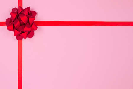 Flat lay composition with decorative red ribbon bow on pink background with copy space for text. Giving presents concept. Greeting card or holidays sale background, selective focus