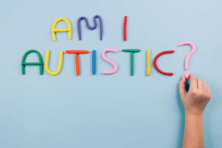 World Autism Awareness Day concept, symptoms - multicolored letters, Am I Autistic - on light blue background with child hand. Autism spectrum disorder and child mental health concept, selective focus