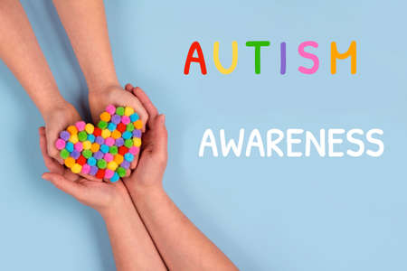 World Autism Awareness Day concept - autistic child's hands supported by mother holding multicolored heart on blue background. Autism spectrum disorder and child mental health concept, selective focus