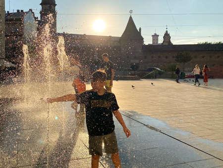 Lviv, Ukraine - September 2, 2020 : children playing and relaxing near pedestrian fountain on Mytna Square in Lviv on sunset. Selective focus