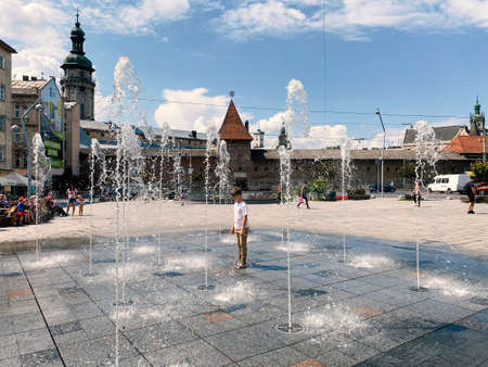 Lviv, Ukraine - September 2, 2020 : tourists and local people relaxing near pedestrian fountain on Mytna Square in Lviv on sunset. Selective focus Editorial