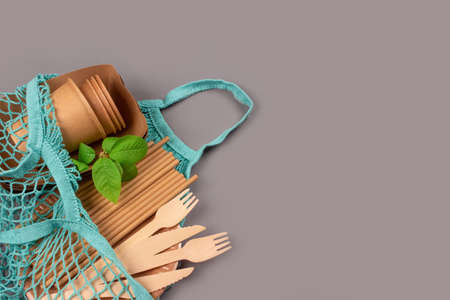 Eco-friendly tableware - kraft paper food cups and containers with wooden cutlery in blue cotton net bag on gray background with copy space. Street food take away paper packaging Standard-Bild