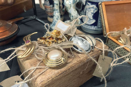 Antiques on flea market or festival - close up view of vintage jewelry, silver brooches and other vintage things. Collectibles memorabilia and garage sale concept, selective focus