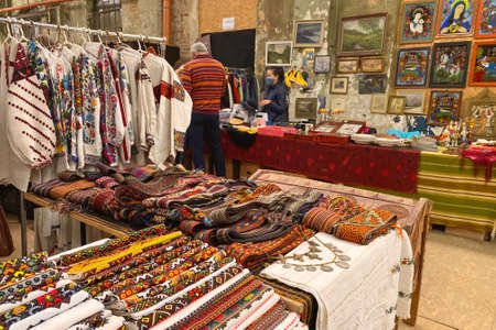 Lviv, Ukraine - May 31, 2021 : garage sale in town hall, Tlum and Kram. Ukrainian clothes - traditional embroidered shirts. Secondhand goods on flea market, thrift shopping concept. Selective focus
