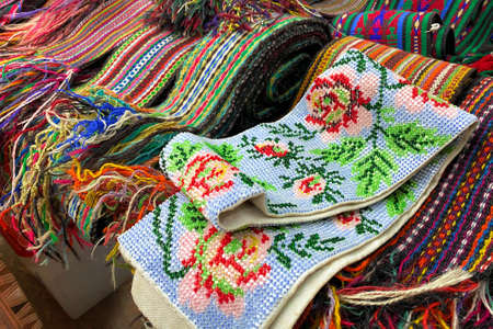 Close up of ukrainian clothes - traditional embroidered shirts and beaded belts. Secondhand goods on flea market or traditional festival, thrift shopping concept. Selective focus