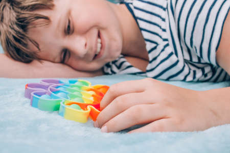 Smiling boy playing with rainbow pop it fidget toy. Push bubble fidget sensory toy - washable and reusable stress relief toy. Antistress toy for child with special needs. Mental health concept