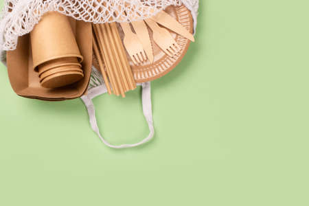 Eco-friendly tableware - kraft paper food cups, plates and containers with wooden cutlery in cotton bag on green background with copy space. Street food paper packaging, sustainable packaging concept