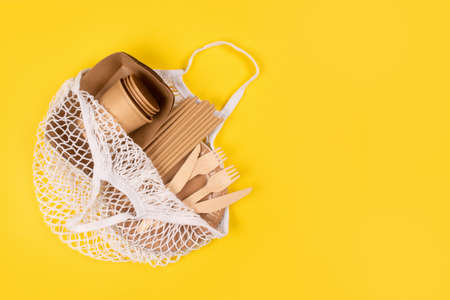 Eco-friendly tableware - kraft paper food cups, plates and containers with wooden cutlery in cotton bag on yellow background with copy space. Street food paper packaging, sustainable packaging concept Standard-Bild