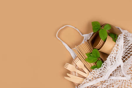 Kraft paper food cups, plates and containers with wooden cutlery in white cotton net bag on brown background with copy space. Street food take away paper packaging, selective focus Standard-Bild