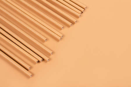 Close up view of eco-friendly paper drinking straws on light brown paper background with copy space. Sustainable paper packaging concept. Selective focus