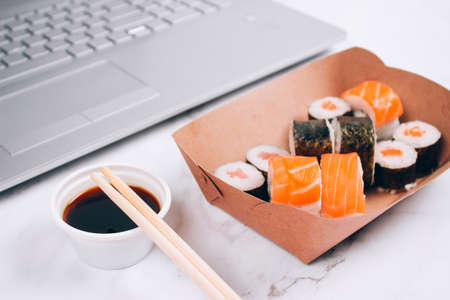 Different sushi rolls with salmon in delivery paper box on white marble table background with laptop - futomaki, uramaki and hosomaki. Online order food and delivery food concept Standard-Bild