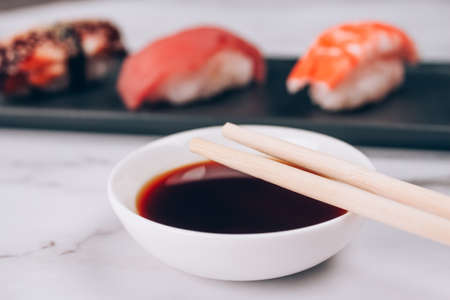 Soy sauce and chopsticks on white marble table against traditional japanese nigiri sushi as background - with raw tuna, salmon fish, shrimp and eel. Asian food delivery and sushi bar menu concept Standard-Bild