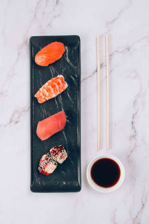 Set of traditional japanese nigiri sushi, soy sauce and chopsticks on white marble table background - with raw tuna, salmon fish, shrimp and eel. Asian food delivery and sushi bar menu concept