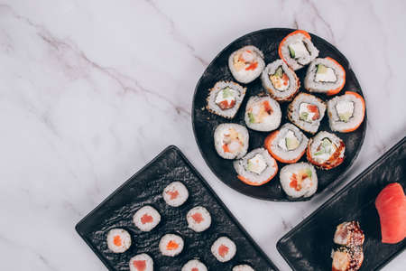 Sushi bar lunch menu - different sushi rolls with salmon, avocado and smocked eel on white marble table background with copy space - futomaki. uramaki, maki. Order food online, delivery food concept
