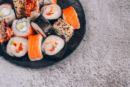 Sushi bar lunch menu. Top view of sushi rolls with salmon, avocado and smocked eel on the concrete table background with copy space. Order food online and home delivery food concept Standard-Bild