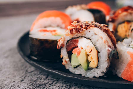 Closeup view of sushi rolls with salmon, avocado and smocked eel on the concrete table background - futomaki. uramaki, hosomaki. Order food online and home delivery food concept. Sushi bar lunch menu Standard-Bild
