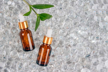 Mockup image of two dropper bottles with natural organic herbal cosmetic oil on light background of water gel balls. Trendy flat lay composition with copy space. Modern organic apothecary concept