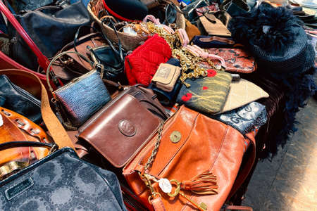 Lviv, Ukraine - May 16, 2021 : vintage luxury leather bags and other vintage things on flea market or seasonal festival, garage sale. Thrift shopping and reusable goods concept