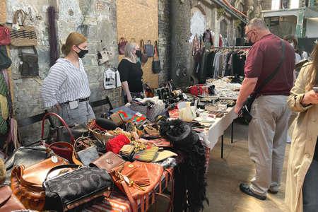 Lviv, Ukraine - May 16, 2021 : people wearing face masks shopping on garage sale in Lem Station. Hipster vintage goods on flea market. Thrift shopping, reusable concept. Vintage bags and clothes