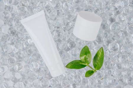 Mockup white cream container and tube - natural body or face creams on light background with water gel balls. Natural organic herbal cosmetics concept . Trendy still life composition with copy space