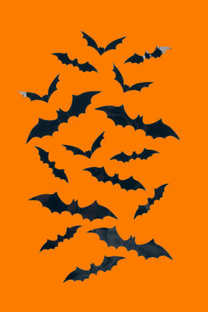 Halloween background - decorative paper bats on orange background with copy space. Halloween decorations or party invitation concept. Selective focus, vertical image Standard-Bild