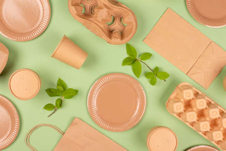 Flat lay composition with eco-friendly tableware and kraft paper food packaging on green background. Sustainable packaging, recyclable paperware, zero waste packaging concept. Selective focus, mockup