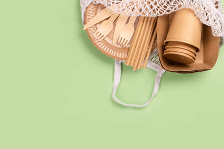 Kraft paper food cups, plates and containers with wooden cutlery in cotton bag on green background with copy space. Street food paper packaging, sustainable packaging concept. Eco-friendly tableware Standard-Bild