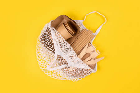 Kraft paper food cups, plates and containers with wooden cutlery in cotton bag on yellow background with copy space. Street food paper packaging, sustainable packaging concept. Eco-friendly tableware