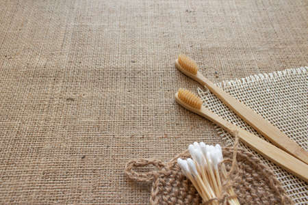 Natural bathroom tools, sustainable zero waste and lifestyle concept. Wooden toothbrushes, bamboo swabs and jute washcloth on fabric background with copy space, mockup