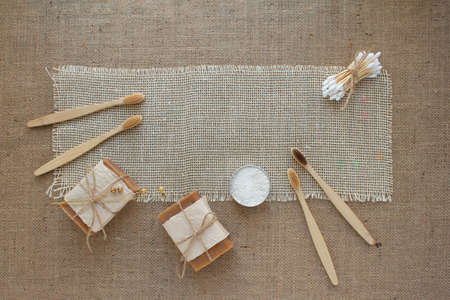 Set of natural bathroom tools, sustainable zero waste and lifestyle concept. Wooden toothbrushes, bamboo swabs, soap, toothpowder on fabric background with copy space, mockup