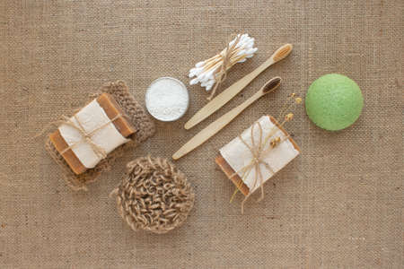 Set of different natural bathroom tools, sustainable lifestyle and zero waste concept. Wooden toothbrushes, bamboo swabs, soap, toothpowder and sponge konjac on fabric background with copy space