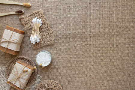 Top view on different natural bathroom tools, sustainable lifestyle, zero waste concept. Wooden toothbrushes, bamboo swabs, soap, toothpowder and jute washclothes on fabric background with copy space