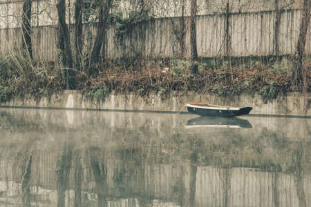 Old abandoned fishing boat on the river or water canal in Milan city on foggy day. Lonely boat under moody sky