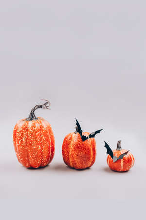 Vertical image, minimal Halloween scary and concept. Decorative orange pumpkins with bats on light gray background with copy space. Halloween decorations or party invitation. Selective focus