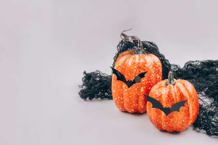 Minimal Halloween scary and funny concept. Decorative orange pumpkins with bat shape mustache on light gray background with copy space. Halloween decorations or party invitation. Selective focus