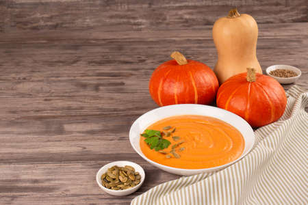Pumpkin cream soup in white bowl toped with parsley and pumpkin seeds on wooden table background with copy space for text. Vegan food concept, homemade soup recipe. Selective focus