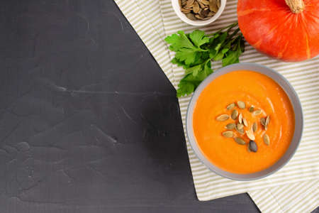 Top view on hokkaido pumpkin cream soup in gray bowl toped with pumpkin seeds on dark stone table background with copy space for text. Vegan food concept, homemade soup recipe. Selective focus Standard-Bild