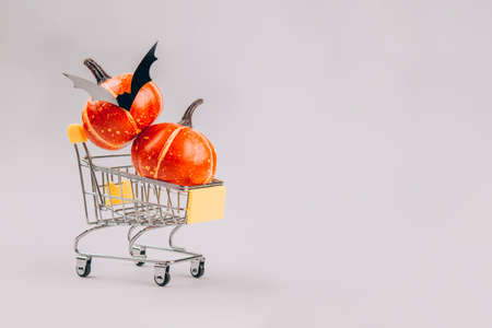 Decorative orange pumpkins inside shopping tray or cart trolley on light gray background with copy space. Halloween scary and funny concept. Halloween sale concept, selective focus