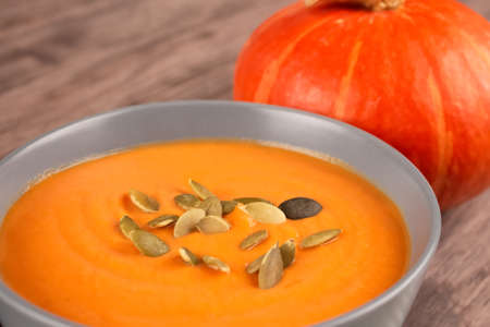 Closeup view on gray bowl with pumpkin cream soup toped with pumpkin seeds on wooden table background with copy space for text. Vegan food concept, homemade soup recipe. Autumn food. Selective focus