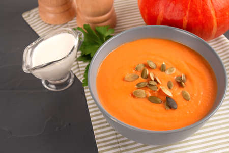 Pumpkin cream soup in gray bowl toped with pumpkin seeds on gray table background with copy space for text. Vegan food concept, homemade soup recipe. Autumn food. Selective focus
