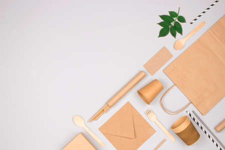 Flat lay composition with eco-friendly tableware - kraft paper food packaging on light gray background with copy space. Street food paper packaging, recyclable paperware, zero waste packaging concept