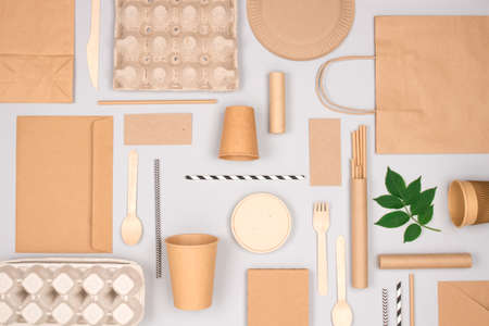 Different eco-friendly tableware and kraft paper food packaging on gray background. Street food paper packaging - cups, plates, straws, containers and paper bags. Mockup, flat lay. Selective focus