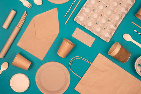 Flat lay with eco-friendly tableware and sustainable packaging. Kraft paper food packaging on green background. Street food paper packaging, recyclable paperware, zero waste packaging concept Standard-Bild