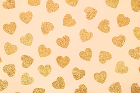 Golden festive background with glitter hearts - St. Valentines Day celebration concept. Love backdrop for greeting card, copy space for your text, selective focus. Toned image