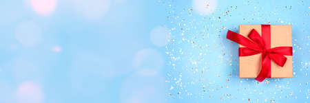 Festive banner with gift box on ligth blue background with bokeh lights around with copy space. Flat lay style for Christmas, New Year, birthday celebration or holidays sale concept Standard-Bild