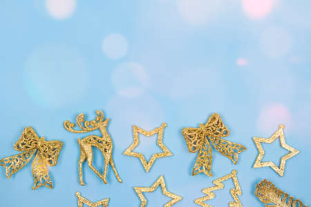 Christmas and New Year festive background with golden decorations on pastel blue background with bokeh lights. Festive frame with copy space for your text. Selective focus