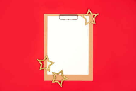 Blank notepaper with golden stars decorations around on bright red background. Flat lay style, planning concept. Selective focus Standard-Bild