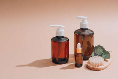 Set of natural bathroom amenities - glass dropper bottles with natural organic cosmetics, natural face or body dry brush, eucalyptus oil, cream, lotion, essential oils on brown background, mockup