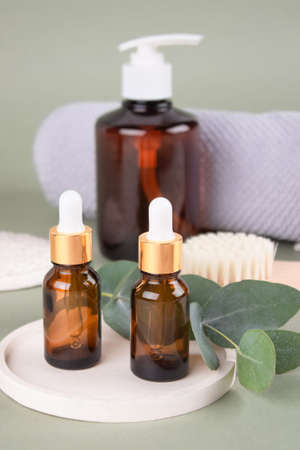 Set of natural beauty treatments - glass dropper bottles with natural organic cosmetics, natural face or body dry brush, eucalyptus oil, cream, lotion, essential oils on green background, mockup