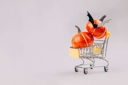Orange pumpkins inside shopping tray or cart trolley on light gray background with copy space. Halloween scary and funny concept. Halloween sale concept, selective focus Standard-Bild